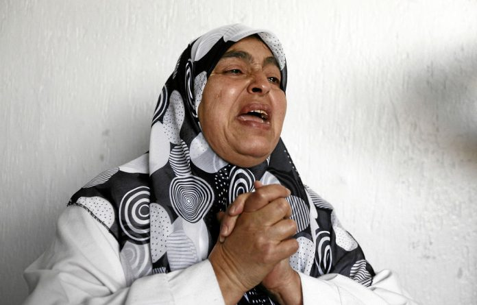 A woman cries for a relative who was hurt in fighting in the town in March.