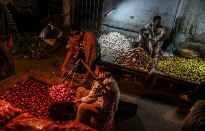 A trader weighs onions at a New Delhi market. India's unemployment rate is about 7%