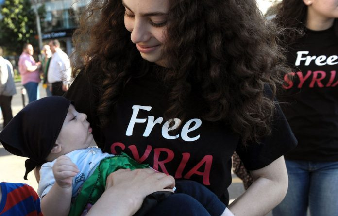 A woman of the Syrian community in Romania holds a baby during a protest against the violence in Syria in Bucharest