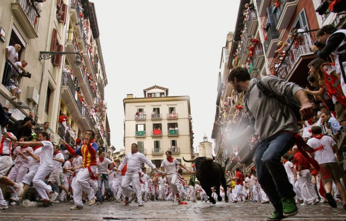 Revelers run on the Estafeta corner as a fighting bull from Miura ranch charges through the streets during the second running of the bulls at the San Fermin fiestas