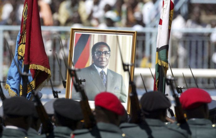 Zimbabwean soldiers carry a portrait of President Robert Mugabe. Senior army figures are now openly muscling in on Zanu-PF to entrench their power and want to stand in party primaries.