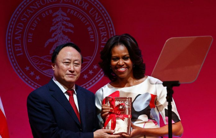Michelle Obama receives a book from Peking University Communist Party secretary Zhu Shanlu after her speech.