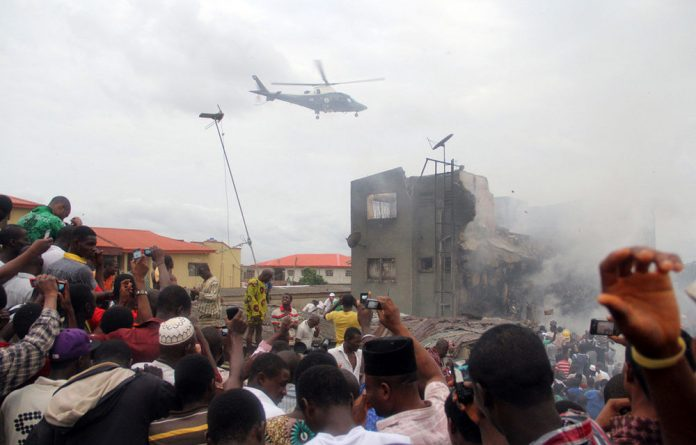 A helicopter hovers over the scene of the crash of a Dana Airline plane that crashed in Lagos