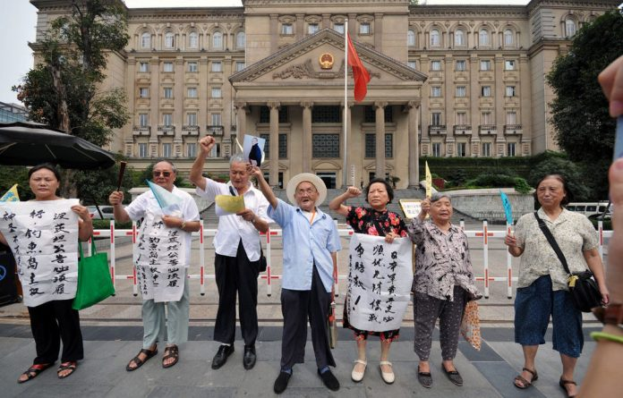 Chinese protesters denounce Japan's claim to the disputed Diaoyu/Senkaku islands outside the Chongqing Municipal Superior People's Court.
