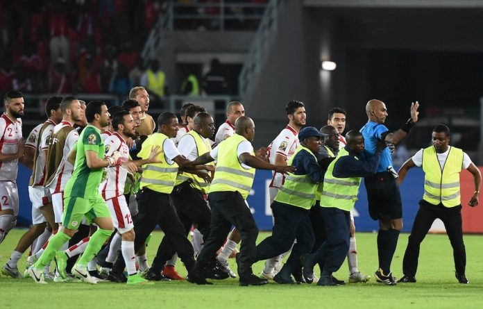 Enraged Tunisian players pursue referee Rajindraparsad Seechurn off the field after the quarter final against Equatorial Guinea last weekend.