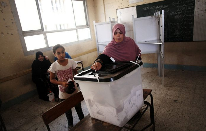 An Egyptian woman casts her vote at a polling station during the second day of the presidential runoff election in Alexandria