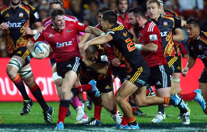 Colin Slade of the Crusaders takes on the Chiefs defence during the Chiefs and Crusaders Super Rugby match at Waikato Stadium.