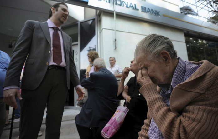 A bank manager explains the situation to pensioners waiting outside a branch of the National Bank of Greece hoping to get their pensions