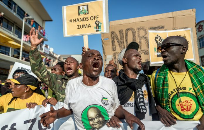 Graft: Jacob Zuma's backers rally at the Durban court where he appeared on corruption charges linked to the arms deal.