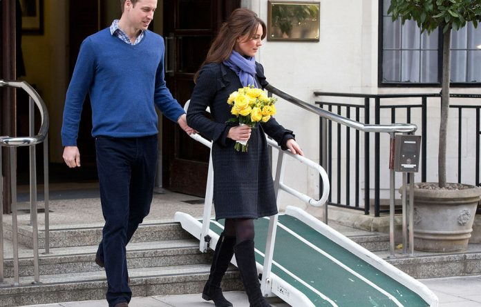 Britain's Prince William stand next to his wife Kate
