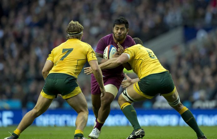 England's Manu Tuilagi tries to break through the defence of Australia's flankers David Dennis