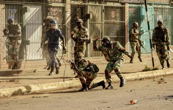 A soldier fires shots at demonstrators in Harare as protests erupted over alleged fraud in the country's election.