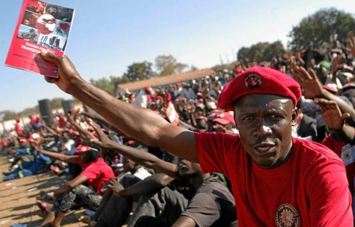 Sick of poverty: A supporter of the MDC-T's Morgan Tsvangirai waves a pamphlet at an election rally.