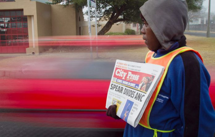 A newspaper vendor sells copies of the City Press on Sunday.