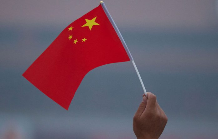A man waves a Chinese flag as people gather to watch the daily national flag raising ceremony in Tiananmen Square in Beijing early on June 3 2012.
