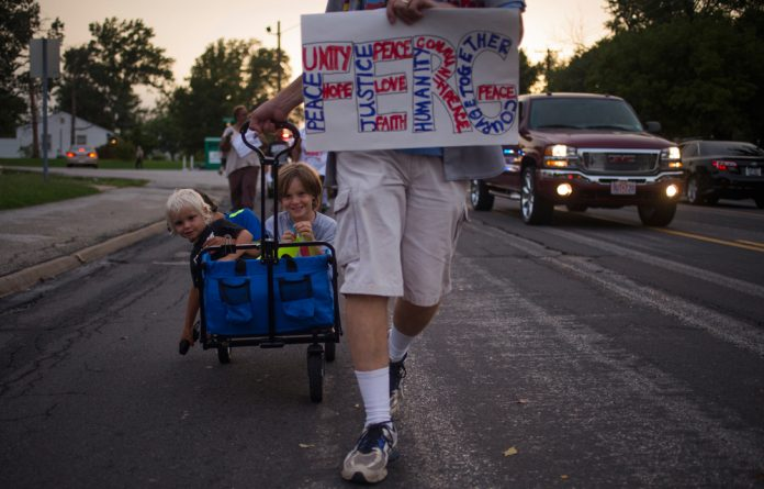 Dwayne Isgrig pulls his children through Ferguson on August 26 while taking part in a protest against the death of teen Michael Brown.