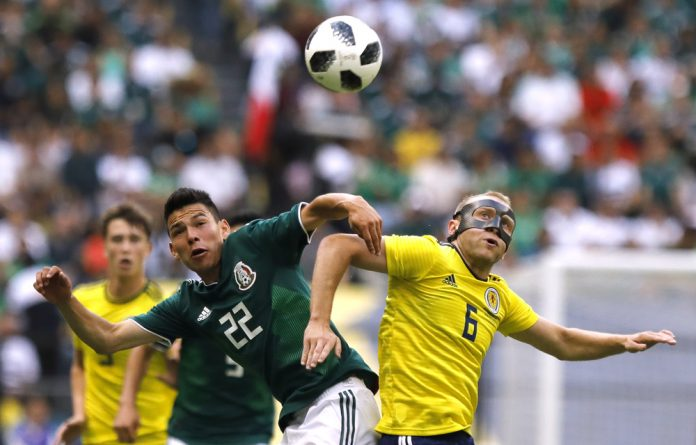 Mexico's Hirving Lozano in action with Scotland's Dylan McGeouch.