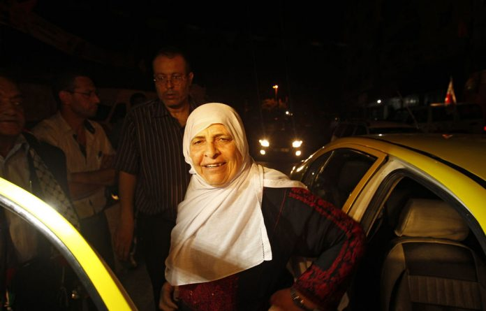 The mother of a Palestinian prisoner in an Israeli prison arrives to join a group travelling by bus across the Erez border crossing in Beit Hanun to see her son during the first visit by the International Committee of the Red Cross early on Monday.