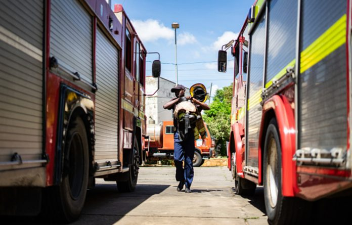 A firefighter prepares for deployment on January 26 at the main fire station in Famona district