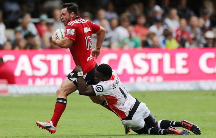 That sinking feeling: Sharks winger Lwazi Mvovo makes a futile attempt to tackle Crusaders centre Ryan Crotty during last weekend's match in Durban.