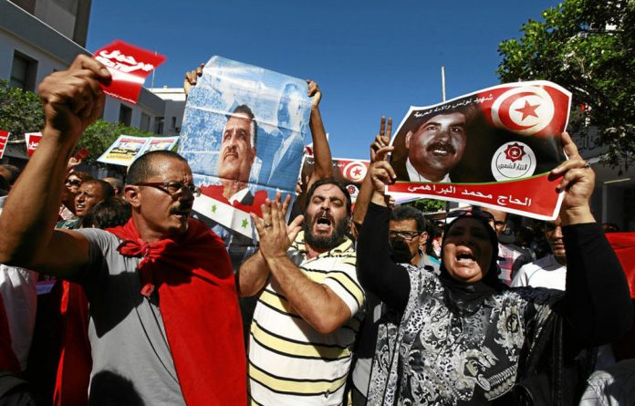 Protesters in Tunisia call for the conservative religion-led government to resign after the death of Mohammed Brahmi.