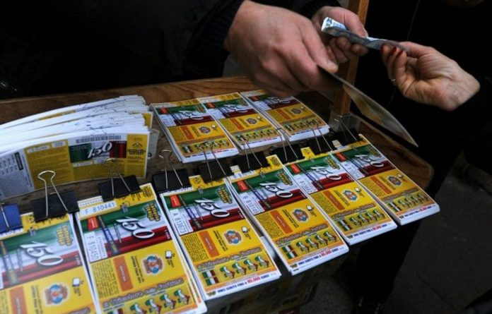 A woman buys lottery tickets at a street seller on January 5