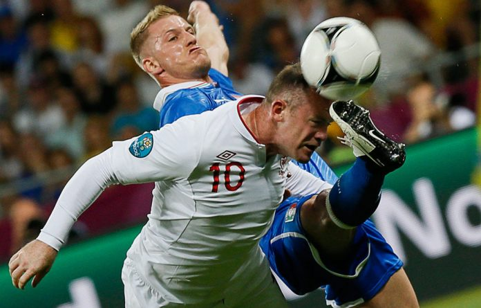 Italy's Ignazio Abate challenges England's Wayne Rooney during their Euro 2012 quarterfinal soccer match at the Olympic stadium in Kiev on Sunday.