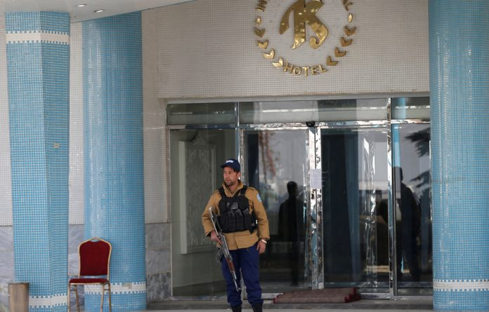 An Afghan security guard stands at the entrance gate of the Intercontinental Hotel after an attack in Kabul