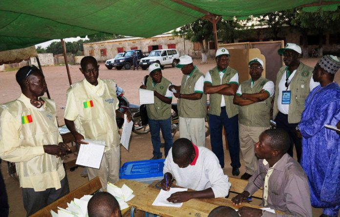 A delegation of the Ecowas observer mission monitor the counting of cast votes at a polling station in Bamako.