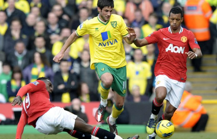 Norwich City's Andrew Surman tangles with Manchester United's Danny Welbeck and Nani.