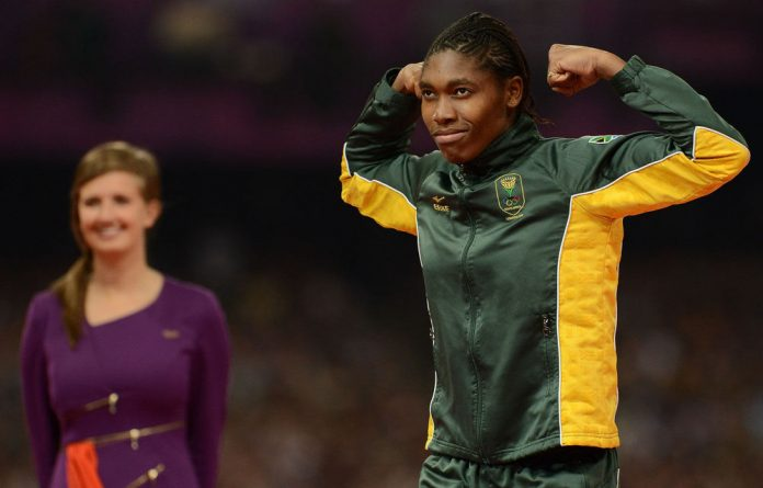 Caster Semenya of South Africa bulges her biceps on the podium before receiving her silver medal in the women's 800m during the evening session of athletics at the Olympic Stadium.