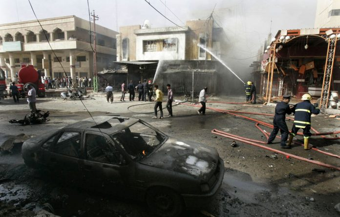 Firefighters hose down a ­building following a car-bomb attack in the Iraq city of Kirkuk in June.