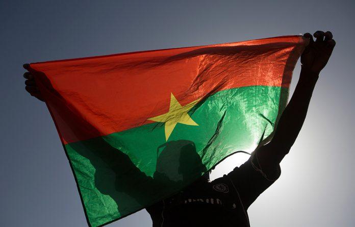 A pro-democracy protester holds up a Burkina Faso flag at Place de la Nation in capital city Ouagadougou.