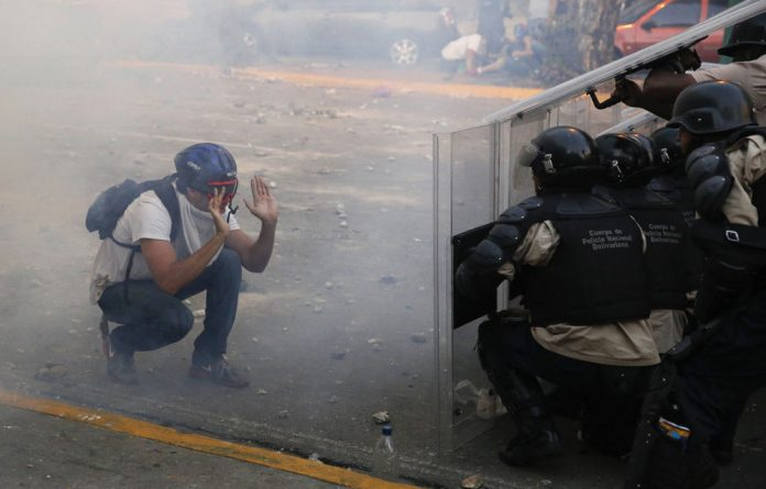 An opposition demonstrator confronts riot police in Caracas.