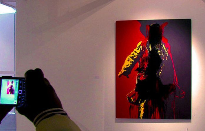 A visitor photographs a painting of President Jacob Zuma at the Goodman Gallery in Johannesburg on May 18.