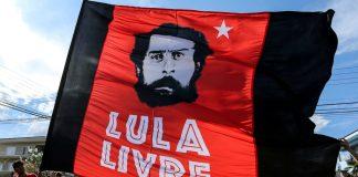 Supporters of former Brazilian President Luiz Inácio Lula da Silva hold a flag next to Federal police headquarters in Curitiba