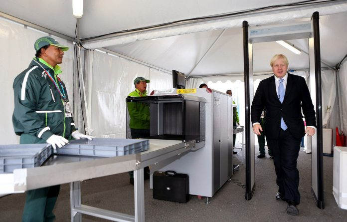 Mayor of London Boris Johnson goes through a security procedure as he visits the London 2012 Olympic Athletes Village.