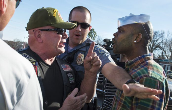 A Ferguson police officer tries to separate a supporter of Michael Brown