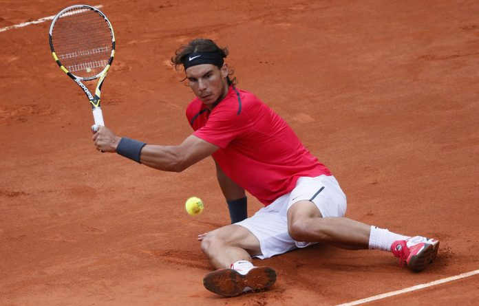 Rafael Nadal hits a return to David Ferrer after falling during their semifinal tennis match of the French Open.