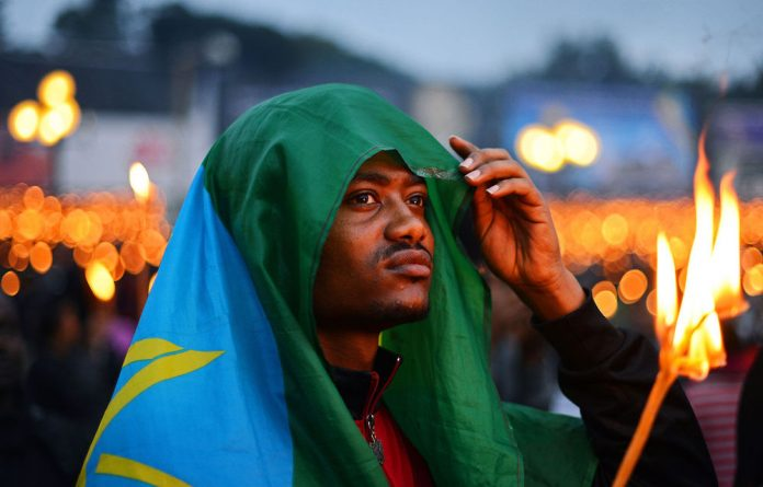 A man wearing an Ethiopian flag takes part in a candle lit vigil in Meskal square for Ethiopian Prime Minister Meles Zenawi who died on August 20
