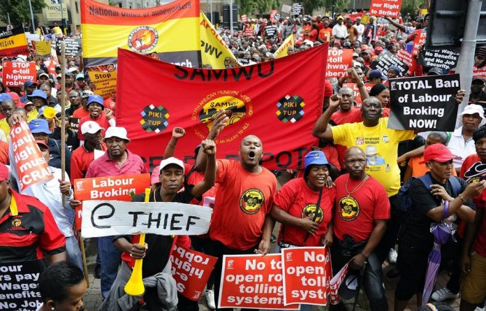 Cosatu members march through Johannesburg with thousands of protesters on March 7 2012 during a demonstration against new tolls on highways between Johannesburg and Pretoria.