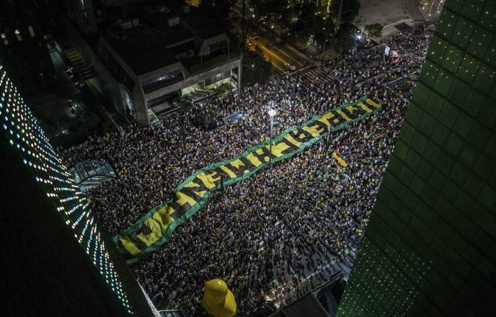 Justice: Demonstrators in São Paulo protest against corruption linked to the government and a state-run oil company. Tens of thousands of Brazilians marched in other cities.