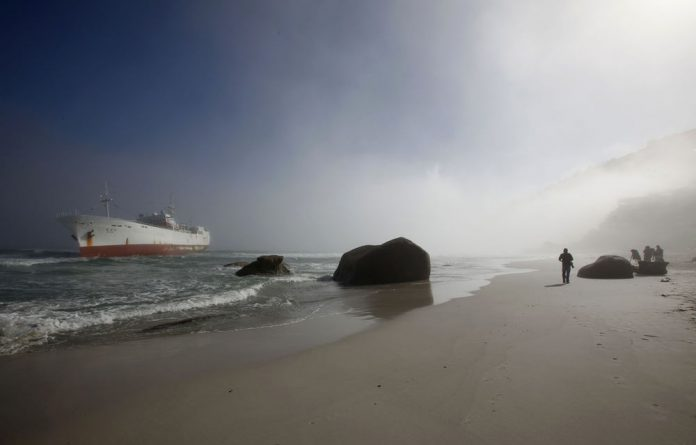 Onlookers walk past a stranded Taiwanese fishing trawler off Cape Town's Clifton beach on May 12.