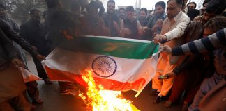 People burn a poster depicting India's flag against what they call airspace violation by the Indian military aircrafts