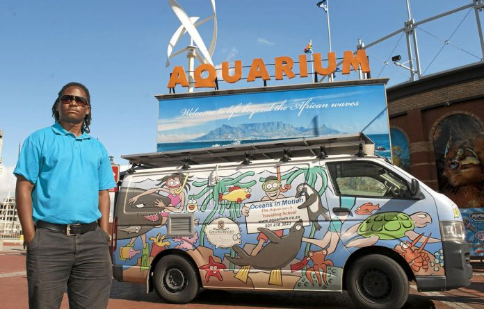 Thabo Sabeko with the van in which he transports sea creatures to schools.