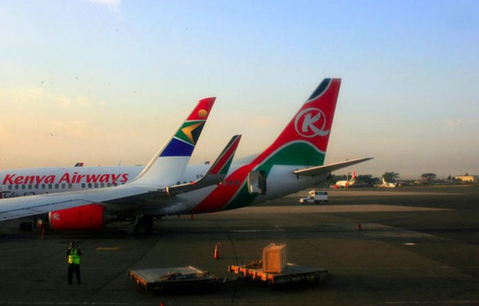 Kenya Airways and South African Airlines planes at sunset in Nairobi's Jomo Kenyatta International Airport.
