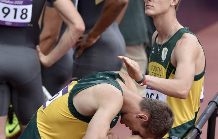 Willem De Beer consoles teammate Shaun De Jager after they failed to complete their men's 4 X 400-meter relay heat the athletics in the Olympic Stadium at the 2012 Summer Olympics