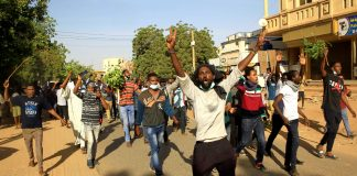Sudanese demonstrators chant slogans as they march along the street during anti-government protests in Khartoum