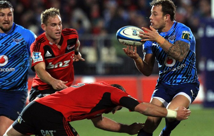 Francois Hougaard of the Bulls gets a pass away as he is tackled by Samuel Whitelock of the Crusaders