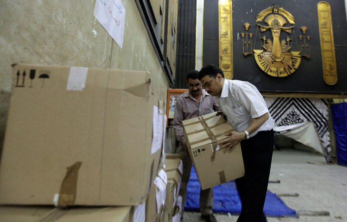 Egyptians carry a box containing ballots for the presidential election at a court in Cairo